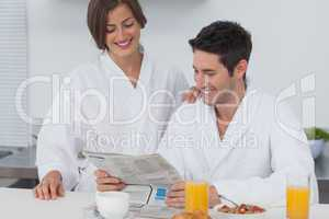 Man reading a newspaper while having breakfast