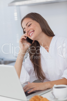 Woman using her laptop while she is phoning