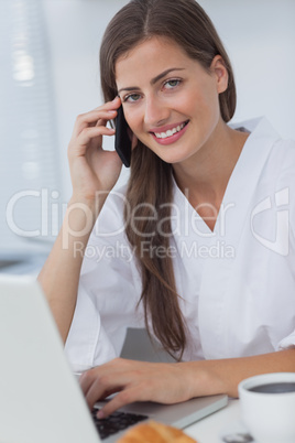 Cheerful woman phoning and using her laptop
