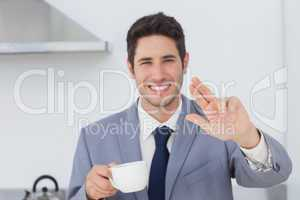 Cheerful businessman waving at someone in the kitchen