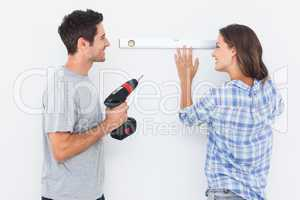 Cheerful man and his wife doing home improvements together