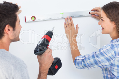 Happy man and his wife measuring together