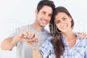 Man and wife holding a key with a house keychain
