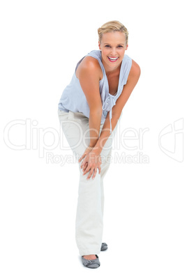 Blonde woman bending and smiling at camera