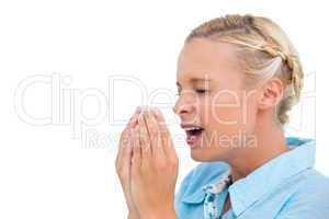 Blonde woman sneezing with hands in front of her face
