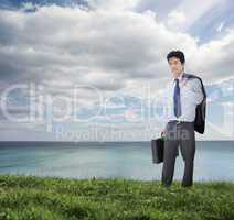 Elegant businessman holding briefcase and his jacket over his sh