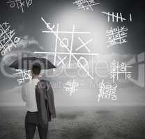 Businessman looking at noughts and crosses