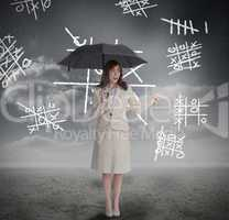 Businesswoman with noughts and crosses holding umbrella