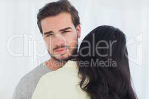 Woman giving hug to uninterested boyfriend