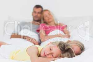 Cute twins sleeping in bed in front of their parents