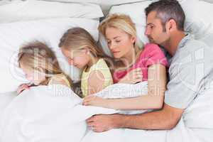 Parents sleeping in bed with their twins