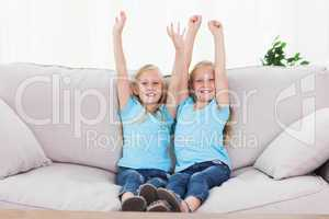 Twins raising their arms sitting on a couch
