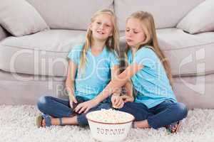 Young twins eating popcorn sitting on a carpet