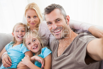 Man taking picture of wife and twins sitting on a couch