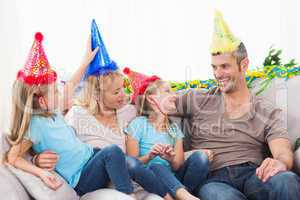 Family celebrating twins birthday sitting on a couch