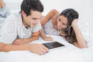 Couple using a tablet lying in bed