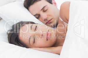 Portrait of an attractive woman sleeping next to her partner