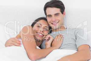 Woman embracing her boyfriend in bed