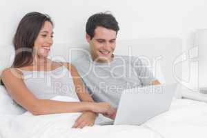 Couple using a laptop together lying in bed