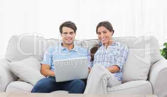 Couple relaxing with a laptop