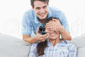 Man hiding his girlfriends eyes and offering her an engagement r