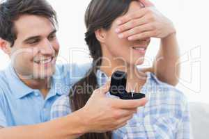 Man hiding his partners eyes and offering her an engagement ring