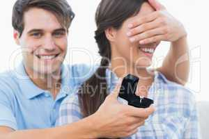 Man hiding his girlfriend eyes and offering her an engagement ri
