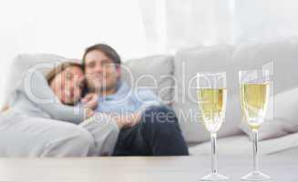 Couple resting on a couch with flutes of champagne