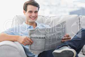 Man reading a newspaper sat on a couch