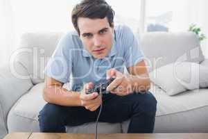 Man playing video games while he is sat on a sofa