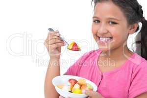 Smiling little girl eating fruit salad
