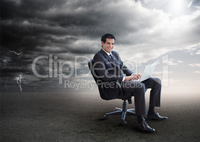 Attractive businessman using his laptop outside during stormy we