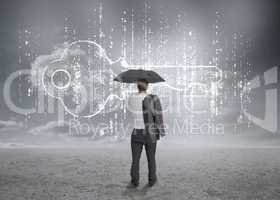 Businessman with an umbrella looking at a big key
