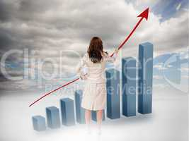 Businesswoman drawing a red arrow over a growing chart