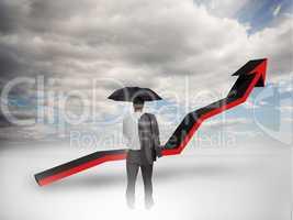 Businessman under an umbrella looking at a red arrow