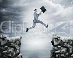 Businessman jumping a gap between cliffs