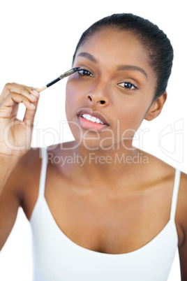 Dark haired woman putting on mascara