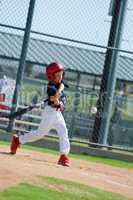 Little league player swinging bat