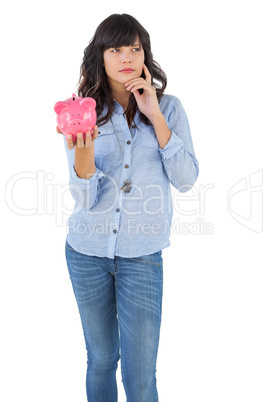 Thinking young woman holding her piggy bank