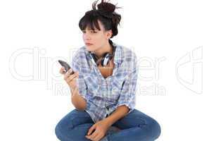 Young woman sitting on the floor with headphones holding her mob