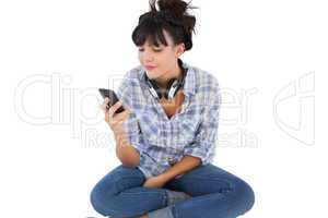 Smiling young woman sitting on the floor with headphones holding
