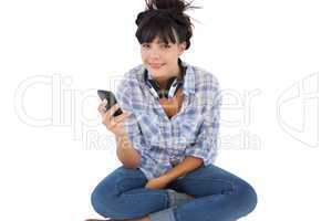 Happy young woman sitting on the floor with headphones holding h