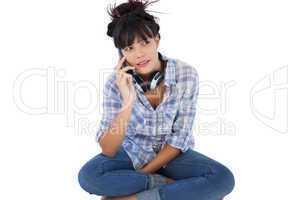 Brunette sitting on the floor with headphones calling someone