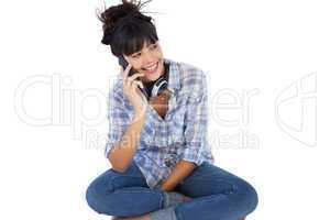 Smiling brunette sitting on the floor with headphones calling so