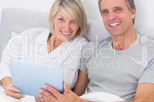 Couple using tablet pc in bed smiling at camera