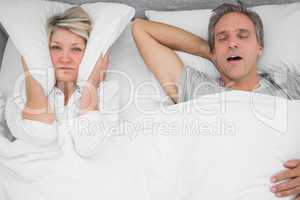 Man snoring loudly as partner blocks her ears