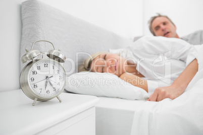 Man looking at ringing alarm clock