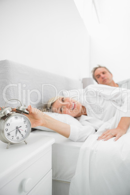 Blonde woman in bed with partner turning off alarm clock