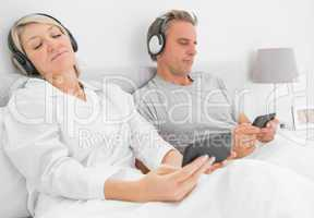 Couple listening to music on their smartphones