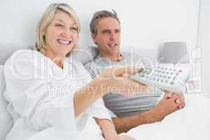 Happy couple watching tv in bed